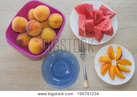 Beautiful sweet peaches and slices of watermelon. Ripe fruit on the table