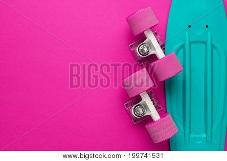 plastic mini cruiser board disassembled on deep pink with background copy space