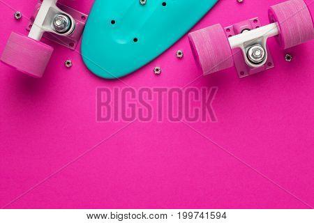 plastic mini cruiser board disassembled. disassembled mini cruiser board on deep pink background. top view of disassembled plastic mini cruiser board. shot of mini cruiser board with copy space.