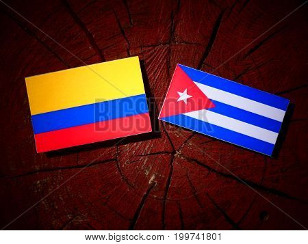 Colombian Flag With Cuban Flag On A Tree Stump Isolated