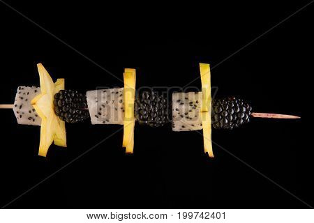 Close-up of a wooden stick with juicy blackberries, yellow sappy carambola, cubes of dragon fruit with black seeds on a dark black background. Exotic snacks. Finger food.