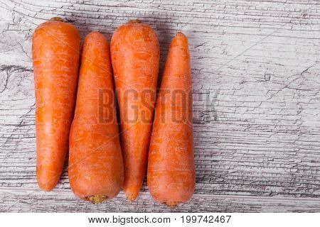 Close-up of four orange carrots on a wooden table, healthy vegetables for diets, wholesome juices and smoothies full of vitamins on a light wooden background, top view.