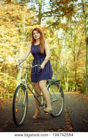 Woodland nature outdoor fitness relax leisure concept. Redhead lady cycling in park. Ginger girl riding on bike through autumnal forest smiling cheering.