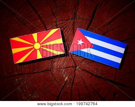 Macedonian Flag With Cuban Flag On A Tree Stump Isolated