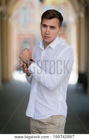 A modern and gorgeous young male walking outside on a dark street background. A confident office worker in a light blue shirt and loose trousers. A man touching his expensive black watch.