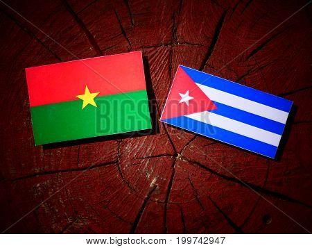 Burkina Faso Flag With Cuban Flag On A Tree Stump Isolated