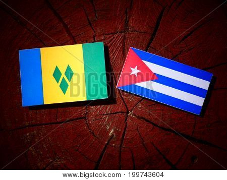 Saint Vincent And The Grenadines Flag With Cuban Flag On A Tree Stump Isolated