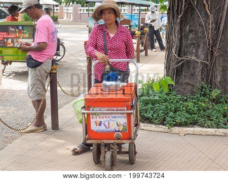 Siem Reap Cambodia - October 29 2016: An unidentified woman selling traditional fruit ice-cream in front of Preah Ang Chek and Ang Chom Shrine Siem Reap Cambodia