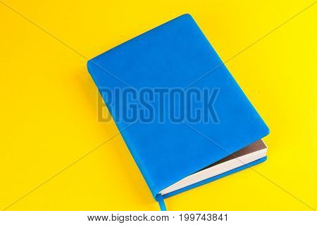 Blue closed diary on a yellow background