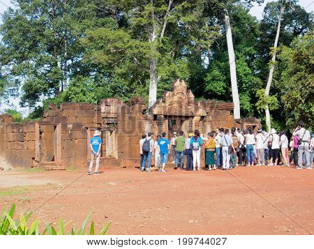 Siem Reap Cambodia - October 30 2016: Asian tourists gather at the entrance of Banteay Srey or Banteay Srei Temple the 10th century Hindu temple in Siem Reap Cambodia.