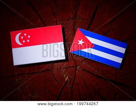 Singaporean Flag With Cuban Flag On A Tree Stump Isolated