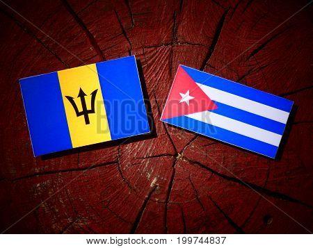 Barbados Flag With Cuban Flag On A Tree Stump Isolated