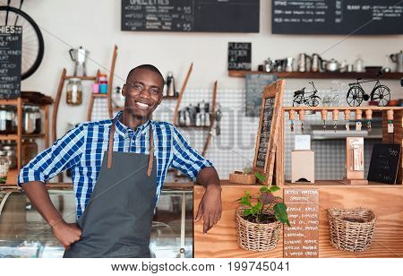 Portrait of a handsome young African entrepreneur wearing an apron smiling and leaning against the counter of his trendy cafe