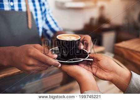Closeup of a barista handing a cup of freshly made cappuccino to a female customer while standing at the counter of a cafe