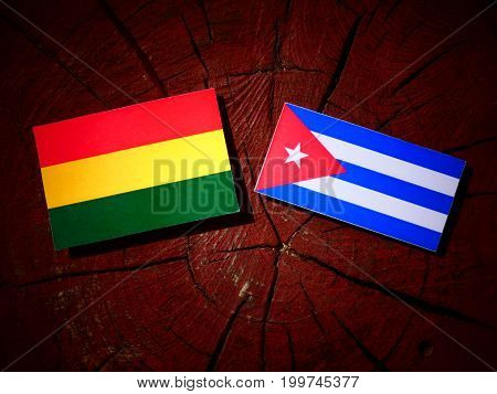 Bolivian Flag With Cuban Flag On A Tree Stump Isolated