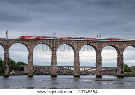 Motion blurred express train crossing the Royal Border Bridge Berwick upon Tweed Northumbria England.