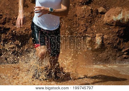 Trail running man in the muddy terrain