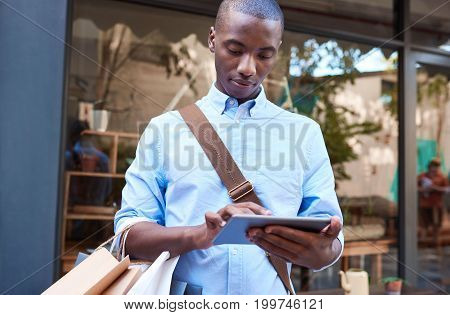 Stylish young African man using a digital tablet while standing with shopping bags in front of a store on a city street