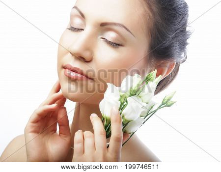 beauty and spa concept: young woman with white flowers isolated on white