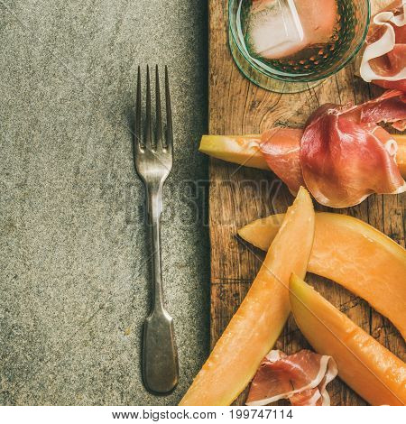 Summer wine party set. Flatlay of Wine snack Prosciutto ham, melon and glasses of rose wine with ice on rustic wooden serving board over grey concrete background. Top view, copy space, square crop