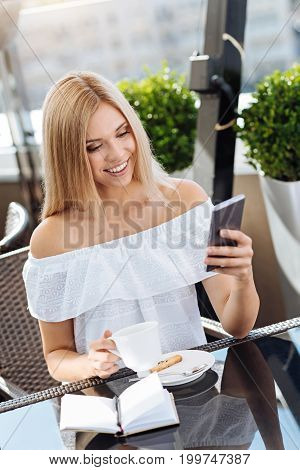 Checking messages. Joyful nice attractive woman holding her smartphone and checking messages while enjoying her morning coffee