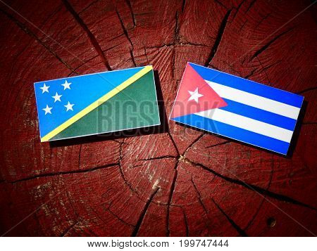 Solomon Islands Flag With Cuban Flag On A Tree Stump Isolated