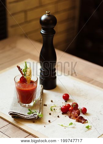 A top view of a glass of Bloody Mary and cherry tomatoes on a white fabric and on a wooden table. Stylish pepper mill and alcohol cocktail with bacon on a top of glass on a blurred background.