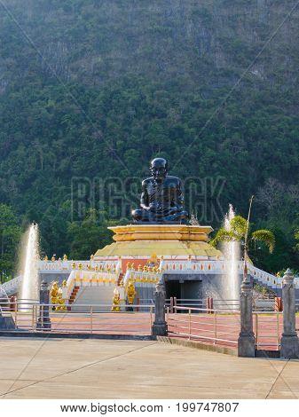Black Statue Of Buddhist Monk Sitting. Elephant Mountain On Background