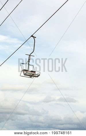 Empty chairlift with blue sky in the background. Cableway chairlift