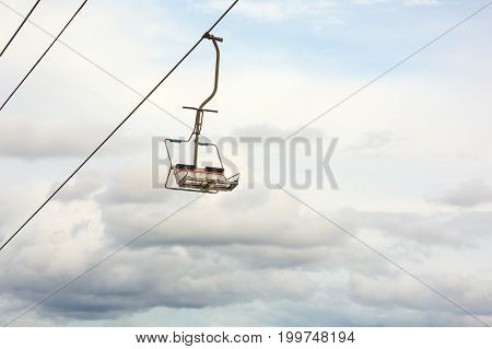 Empty chairlift with cloudy sky in the background. Cableway chairlift