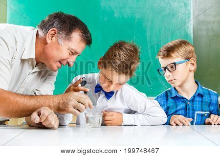 Two schoolboys and their teacher in class at the desk performing experiment against blackboard