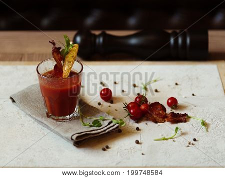 A top view of small tomatoes, peppercorns, herbs and pepper mill on a light fabric on a wooden table. A glass of Bloody Mary with bacon and slice of potato on a top of a glass on a blurred background.