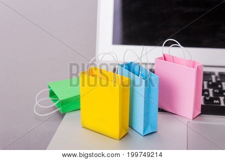 Color packs for purchases and a laptop on a gray background. Copy space for text