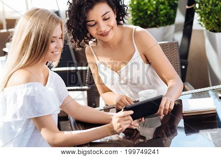 What do you think. Positive cute cheerful woman holding a tablet and showing a picture to her friend while asking her opinion about it