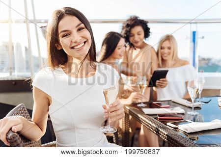 Great time. Happy elated charming woman holding a glass with champagne and smiling while having a great time with her friends
