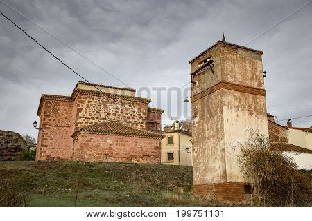 old transformer station and San Juan Bautista church in Chequilla village, Province of Guadalajara, Spain