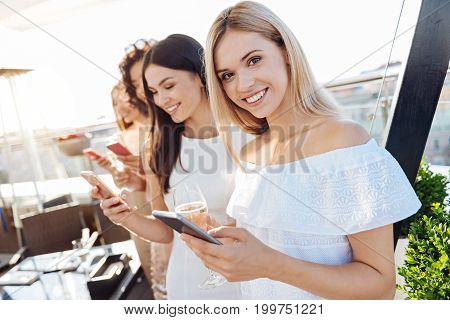 Friendly smile. Cheerful charming blonde woman holding her smartphone and smiling to you while standing on the rooftop with her friends
