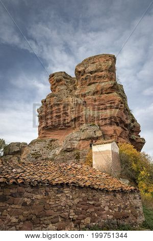 rustic house at the base of red sandstone monoliths in Chequilla village, Province of Guadalajara, Spain