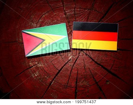 Guyana Flag With German Flag On A Tree Stump Isolated