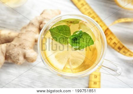 Cup with ginger tea and measuring tape on light table. Weight loss concept