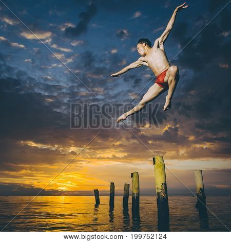 Ballet dancer in the air jumping over the water and beautiful sunset