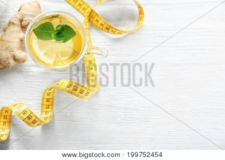 Cup with ginger tea and measuring tape on light wooden table. Weight loss concept