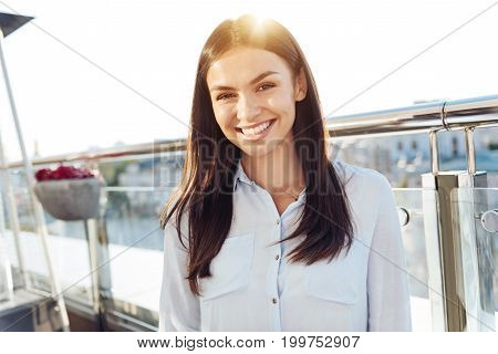 Positive emotions. Happy delighted positive woman looking at you and smiling while feeling great