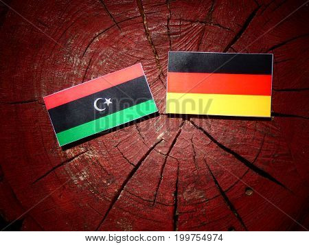 Libyan Flag With German Flag On A Tree Stump Isolated