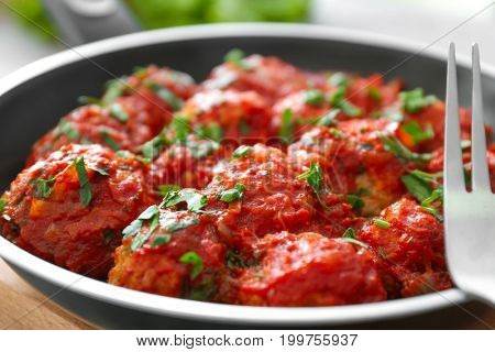 Closeup view of frying pan with turkey meatballs and tomato sauce