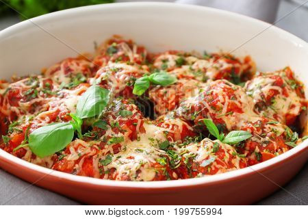 Ceramic casserole dish with delicious turkey meatballs, tomato sauce and melted cheese, closeup