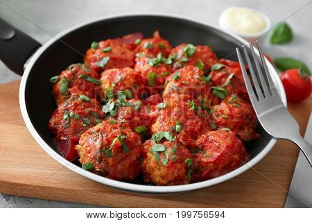 Frying pan with turkey meatballs and tomato sauce on cutting board