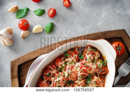 Ceramic casserole dish with turkey meatballs, tomato sauce and melted cheese on light table
