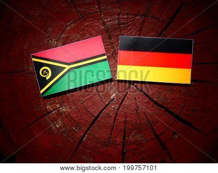 Vanuatu Flag With German Flag On A Tree Stump Isolated