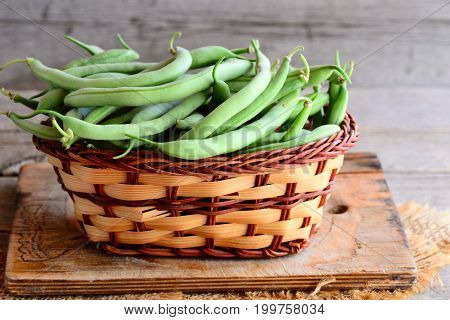 Fresh string beans in a brown wicker basket on a wooden board and a burlap textile. Old wooden background. Closeup